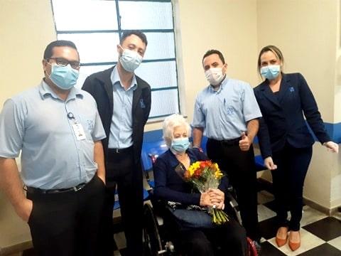 Foto de idosa com buquê de flores e equipe médica ao lado