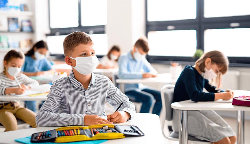 Alunos em sala de aula, usando máscaras de proteção